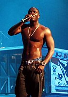 Akon shirtless wearing black pants, singing into a microphone on stage.