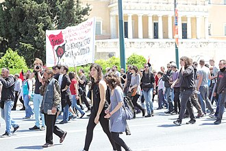 """Anarchism in Greece - Anarchist-communists march in Athens, Greece on 1 May 2014 at Syntagma Square next to the parliament building while holding red-and-black flags (an anarchist-communist symbol) and a banner which reads """"1884-2014 1st May, struggle for a new society without exploitation of human by human until the overturn of the state and the capital, for the worldwide revolution, anarchy and communism.Anarchist newspaper Black Flag and anarchist organization Circle of Fire""""."""