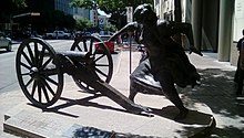 Bronze statue of a woman firing a cannon