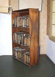 Chiếc tủ sách gỗ ba tầng chứa đầy sách, đặt ở một góc trước lối vào Secret Annexe