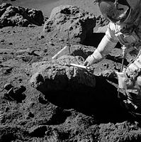A man in a spacesuit leans over a large rock