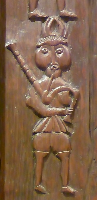 Drone (music) - Carving (c.1600) on an oak bookcase of a bagpiper.