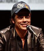A man is seen speaking into a microphone. He is wearing a black leather jacket over a black unbuttoned collared shirt and a black baseball cap.