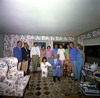Family group portrait in sunroom with flowered drapes and upholstery with all standing behind Joe who is seated, Jackie is kneeling next to him