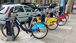 Santander Cycles - Blue (Barclays Cycle Hire), yellow (2014 Tour de France) and red (Santander Cycles) cycles in a docking station.