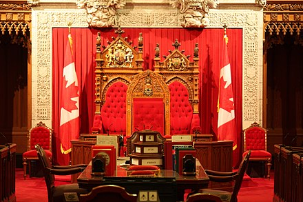 The thrones for the Canadian monarch (back left) and his or her royal consort (back right) in the Senate of Canada; these may also be occupied by the sovereign's representative, the governor general and his or her viceregal consort at the State Opening of Parliament (the speaker's chair is at centre) Canadian-Senate-thrones.jpg