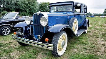 A blue 1920s-style car facing forward but angled towards its right, the picture's left, on a grassy clearing