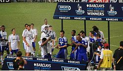 A coloured photograph of the Chelsea squad standing on a podium, celebrating their second Premier League Asia Trophy win.