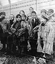 Children in oversized, striped concentration-camp clothing behind a barbed-wire fence