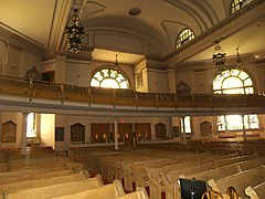 The back of a wide, two to three-story room is visible. Four visible rows of wooden pews lead to the back wall, which has three sets of double doors at its center. A second-floor balcony which projects partway into the sanctuary holds more wooden pews. The back wall has two large arched stained-glass windows visible, and two smaller rectangular ones one each side of the doors. The ceiling is arched, with elaborate chandeliers with Star-of-David shapes hanging from it.