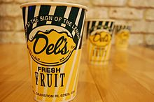 Three paper cups with the Del's Lemonade logo on a wooden table