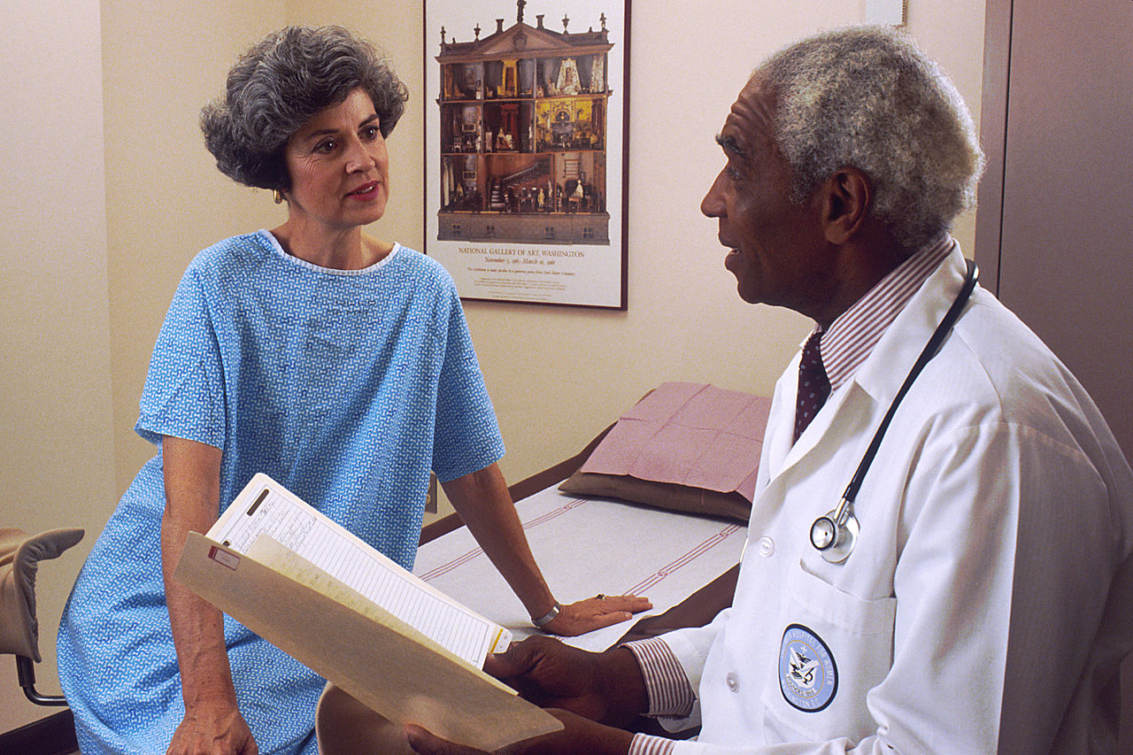 1280px-Doctor_consults_with_patient_%287%29