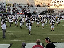 UCF football players, wearing black jerseys, going though warmups