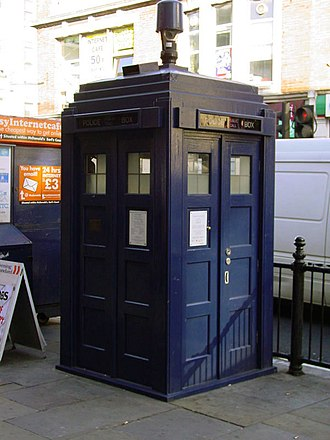 TARDIS - Police box mounted with a modern surveillance camera outside Earl's Court tube station in London