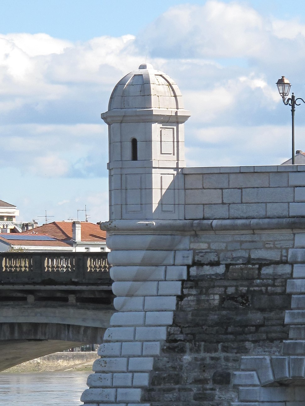 Photographie d'une échauguette de pierre blanche se détachant au-dessus d'un pont.