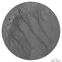 A circular part of a grayish surface, which is intersected from the top-left to the bottom-right by four wide sinuous groves. Smaller and shorter grooves can be seen between them running either parallel to the large grooves or criss-crossing them. There is a rough terrain in the top-left corner.