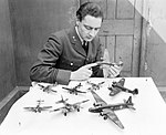 Flight Lieutenant J G Eadie, Medical Officer at RAF No. 11 Group headquarters at Uxbridge, photographed with part of his collection of model aircraft, 16 April 1943. CH9234.jpg