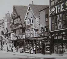 Old photograph of Tudor building with wooden buildings in the protruding upper floors.
