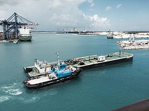 Grand Bahama Port Authority - Tug and barge in Freeport Harbour, with container terminal and shipyards in background.