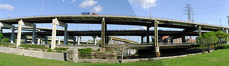 Two elevated roadways with two connecting ramps above a river.