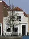 foto van Huis met geverfde ingezwenkte lijstgevel. Staafankers. Voordeuromlijsting