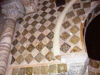 Photographie des carreaux de céramique lustrée, monochromes et polychromes, qui ornent le mihrab et son mur. Leurs décors variés comportent divers ornements géométriques, floraux et végétaux.