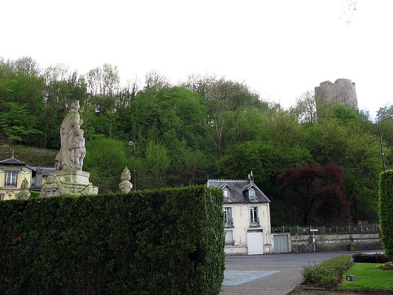 Guise (Aisne, France) - L'arrière du Monument-aux-Morts et le donjon, vus depuis le petit parc. Le Monument-aux-morts est surmonté et décoré par une statue représentant une mère et un enfant. Il est érigé dans le petit parc à l'angle de la rue du Jeu de Paume et du boulevard Jean Jaurès.