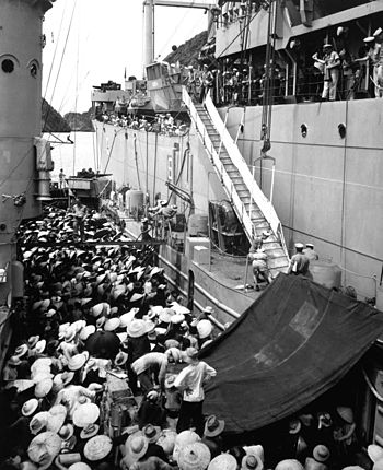 English: Vietnam refugees. USS Montague lowers...