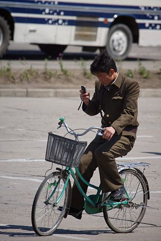 Economy of North Korea - Cyclist uses a mobile phone in Hamhung in 2012.