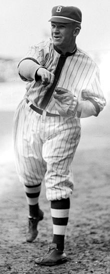 "A man wearing a pinstriped baseball jersey and a cap with the letter ""B"" written on it having just thrown a baseball."
