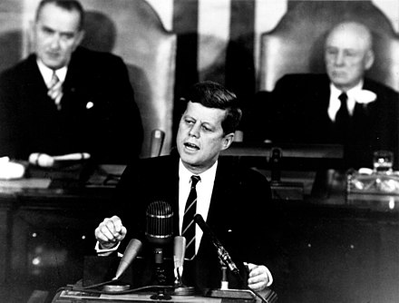 Kennedy proposing a program to Congress that will land men on the Moon, May 1961. Johnson and Sam Rayburn are seated behind him. Kennedy Giving Historic Speech to Congress - GPN-2000-001658.jpg