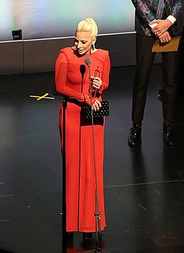 Lady Gaga wearing a red outfit and holding an award