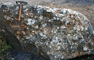 Conglomerate (geology) - Boulder of conglomerate with cobble-sized clasts. Rock hammer for scale.