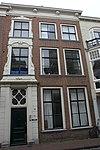 foto van Pand met bakstenen gevel met versierde deurtravee, rechte kroonlijst met consoles, deur en beide vensters erboven in gesneden Lod.XV lijsten