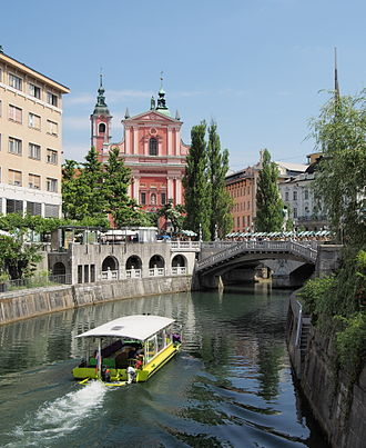 The scenic Triple Bridge, decorated with stone balusters and stone lamps on all of the three bridges Ljubljana in Ljubljanica.jpg