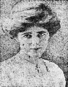 A grainy newspaper photo of a woman in her early 20s who looks straight at the camera. Her hair is coiffed, and she is wearing a white blouse