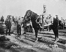 A black-and-white photo of a man, Francisco Madero, on horseback. Other men stand in background.