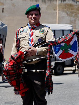 Pipe banner - A Malta Scout bagpiper with pipe banner