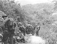 Soldiers that are part of Merrill's Marauders, resting alongside a jungle trail in Burma