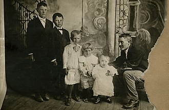 George W. Romney - Gaskell Romney, sitting, and family, of Colonia Dublan, Chihuahua, c. 1908. Son George is fourth from the left.