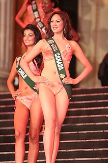 A photograph of four women standing in a row wearing pink bikinis and green sashes with white letters all looking to the left and smiling