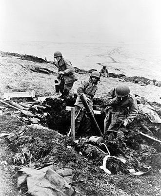 Battle of Attu - U.S. soldiers fire mortar shells over a ridge onto a Japanese position on 4 June 1943.