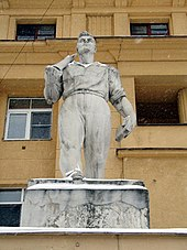Statue of worker in front of tan apartment building
