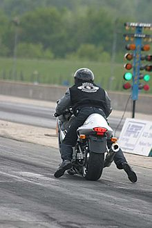 A rider in black jeans and tennis shoes seen from behind on a Suzuki Hayabusa motorcycle, with a green light to his right.
