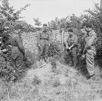 13th/18th Royal Hussars - Operation Overlord (the Normandy Landings)- D-day 6 June 1944. Reverend Victor Leach, Padre of 13/18 Hussars, reading the burial service for a fallen tankman who was killed in action with the German 21st Panzer Division in the Hermanville-sur-Mer sector of Normandy, France. The dead man's comrades stand in silent tribute at the graveside.