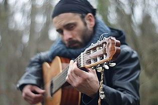 Outtaseezun musician on acoustic guitar.jpg