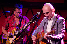 A man at left is playing an electric guitar, while 56-year-old Kelly plays his acoustic guitar. Both are looking down towards their own guitar, each uses a plectrum in their right hand while the left is on the fret board. In front of each is a microphone on its stand.