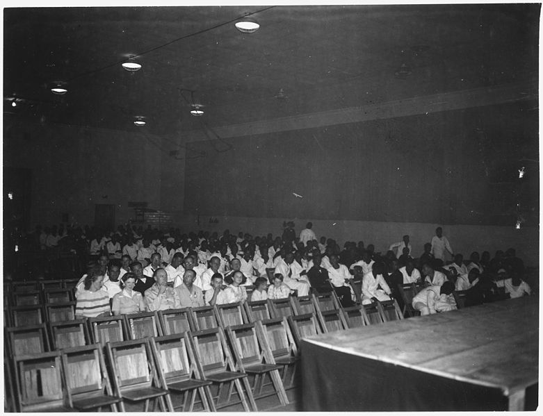 "File:Photograph with caption ""View of Attendance at a Movie in Permanent Recreation Building,"" U.S. Naval Ammunition... - NARA - 283490.jpg"