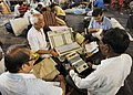 Polling officials checking the Electronic Voting Machines (EVM's) and other necessary belongings for use in the General Elections-2014, at the distribution centre, at Dumurjala Indoor Stadium, in Howrah, West Bengal.jpg