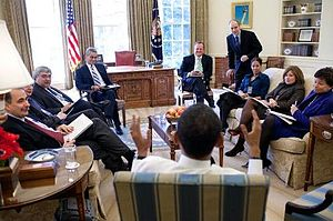 White House Office - President Barack Obama (in the foreground, facing away) meeting April 29, 2009 with senior White House staff. Individuals present (l–r): David Axelrod (Senior Advisor), Jim Messina (Deputy Chief of Staff), Pete Rouse (Senior Advisor), Rahm Emanuel (Chief of Staff), Robert Gibbs (Press Secretary), Phil Schiliro (Director of Legislative Affairs), Mona Sutphen (Deputy Chief of Staff), Alyssa Mastromonaco (Director of Scheduling and Advance) and Valerie Jarrett (Senior Advisor).